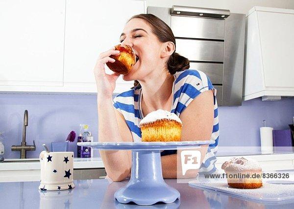 Junge Frau beim Muffinessen