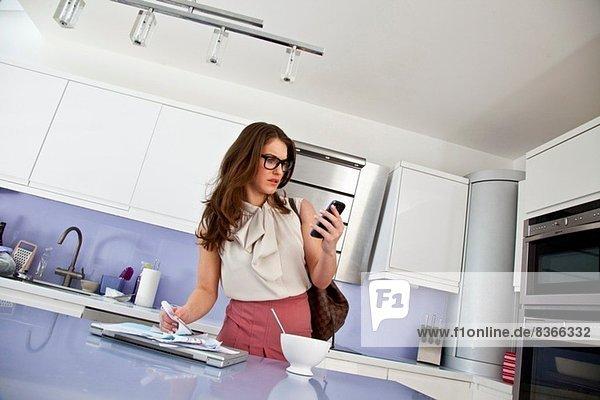 Junge Frau mit Handy und Papierkram beim Frühstück