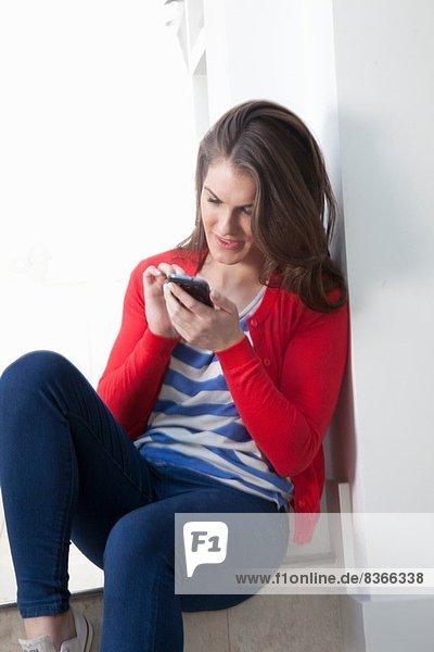Junge Frau sitzend auf Schritt mit dem Handy