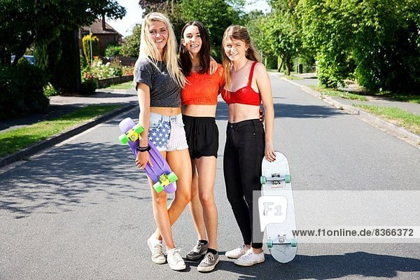 Portrait of three young women with skateboards