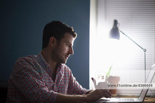 Mann sitzt am Schreibtisch und schreibt Mann sitzt am Schreibtisch und schreibt