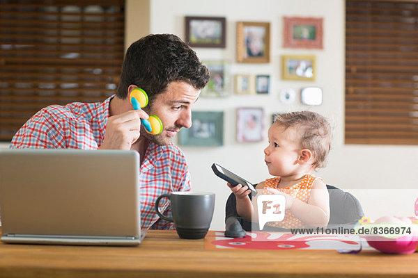 Mann und Baby sitzen am Küchentisch und spielen mit Smartphone und Spielzeugtelefon.