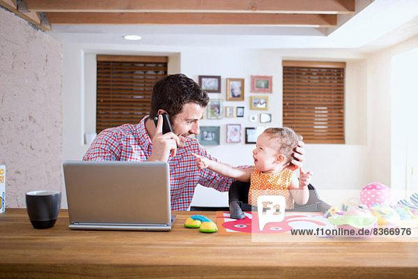 Mann und Baby sitzen am Küchentisch und telefonieren