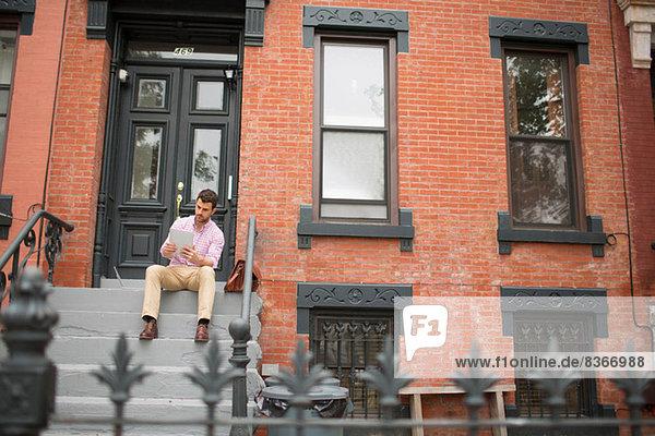 Man sitting on step using digital tablet