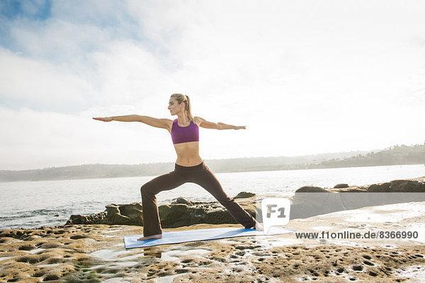 Frau beim Yoga an der Küste