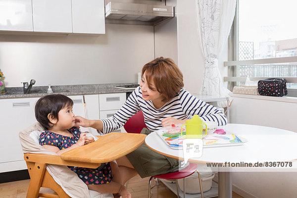 Mutter im Gespräch mit dem Baby am Esstisch