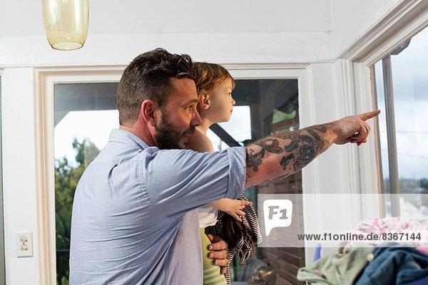Vater und Tochter schauen durchs Fenster