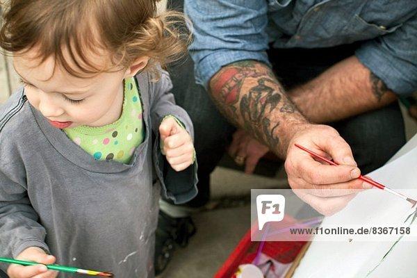 Vater und Töchter malen auf Staffelei