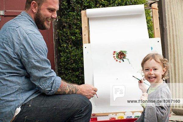 Vater albert herum und macht Farbe auf das Gesicht der Tochter.