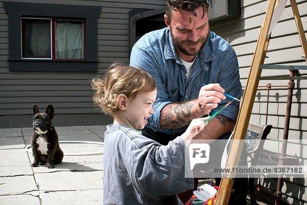 Vater und Tochter im Freien malen auf Staffelei