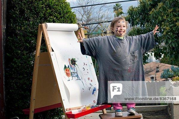 Mädchen im Freien malen auf Staffelei