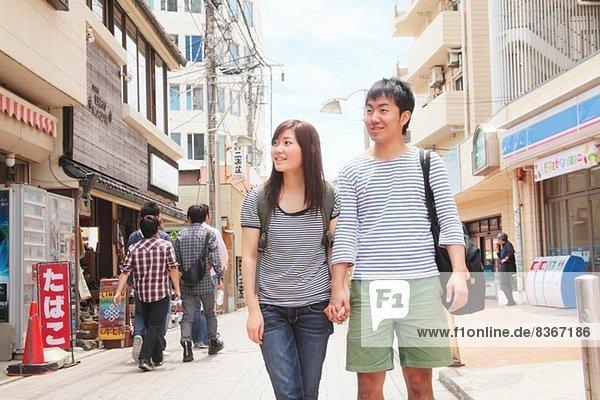 Junges Paar hält sich an den Händen und geht durch Kamakura  Japan