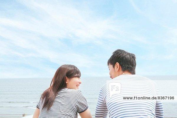Rückansicht des Paares an der Küste  von Angesicht zu Angesicht und lachend