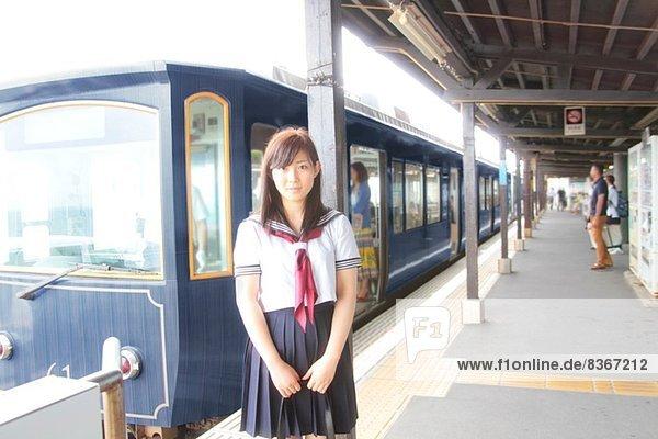 Frau in Schuluniform auf dem Bahnsteig am Bahnhof