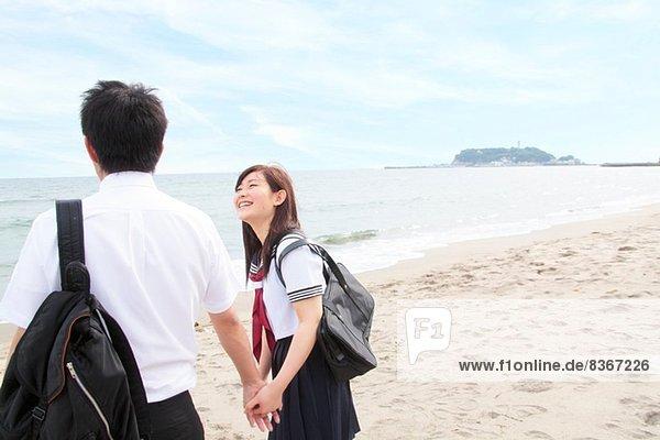 Junges Paar hält Hände am Strand  Rückansicht