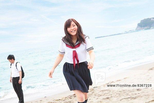 Junge Frau in Schuluniform über den Strand rennend