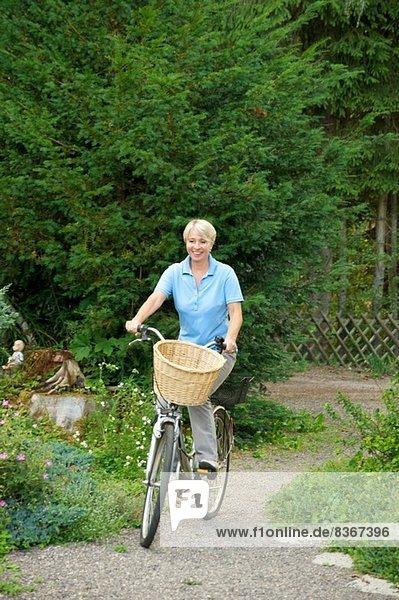 Seniorin auf dem Fahrrad im Park
