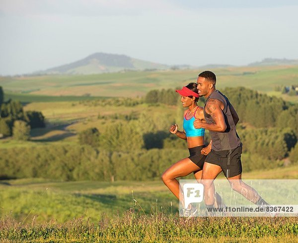 Man and woman running in landscape  Othello  Washington  USA