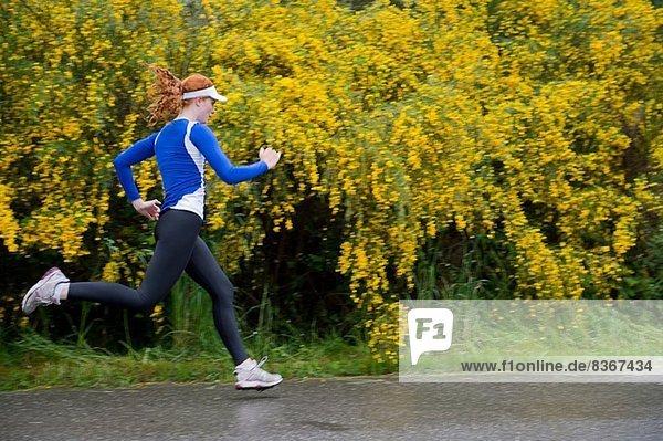 Teenage girl jogging on road  Bainbridge Island  Washington  USA