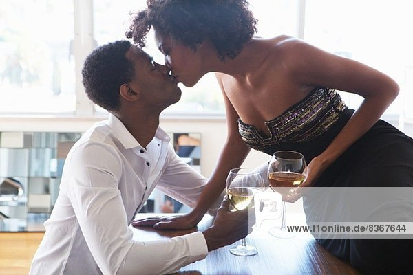 Portrait of young couple with wine  kissing