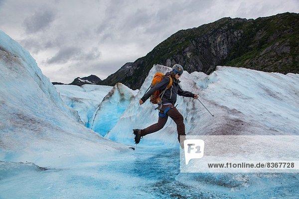 Young man walking on Mendenhall Glacier  Alaska  USA