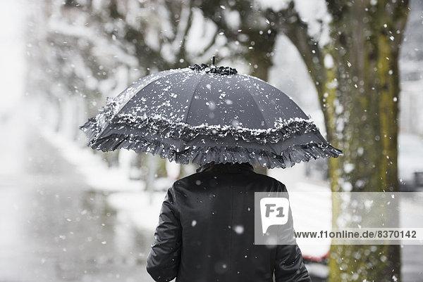 A Woman Walking In A Snowfall With An Umbrella