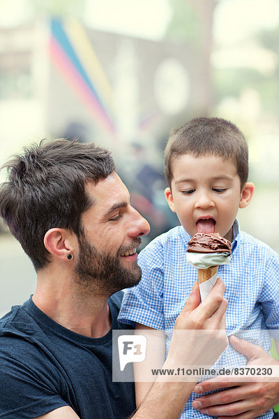 Father holding ice cream  son licking it