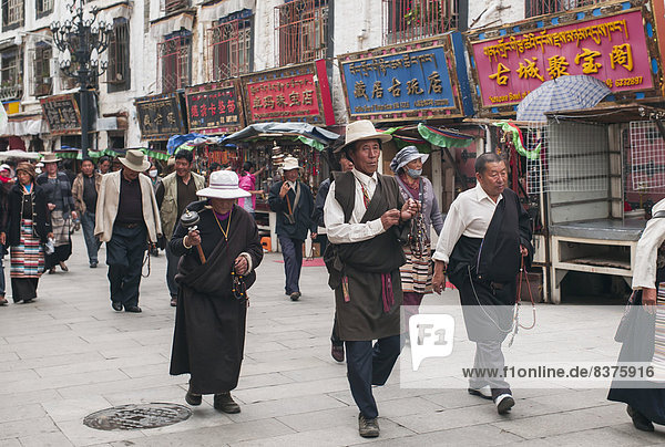 People In A Parade Walking Down A Street  Tibet  China