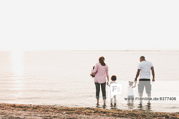 Interracial Family Wading In Water By Beach  British Columbia  Canada