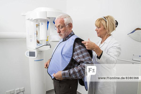 Mann wird fürs Röntgen des Gebisses vorbereitet  mit Bleiweste als Strahlungsschutz  Deutschland
