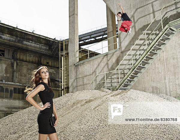 Junge Frau im schwarzen Kleid steht vor einem Zementwerk  junger Mann springt von einem Geländer  Kiefersfelden  Bayern  Deutschland Junge Frau im schwarzen Kleid steht vor einem Zementwerk, junger Mann springt von einem Geländer, Kiefersfelden, Bayern, Deutschland
