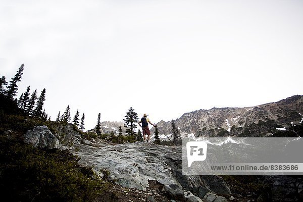 A male hiker on a trail as he attempts to summit a peak on a cloudy day in the North Cascades  WA.