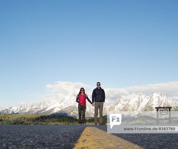 A young couple holds hands in mountains.