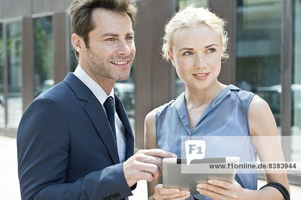Immobilienmakler mit digitalem Tablett  das dem potentiellen Käufer die Immobilie zeigt.