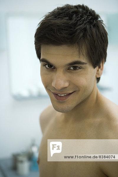 Nackter junger Mann lächelnd vor der Kamera  Porträt