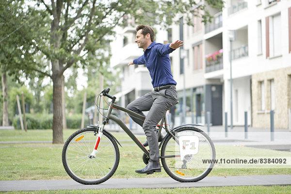 Mann auf dem Fahrrad mit ausgestreckten Armen