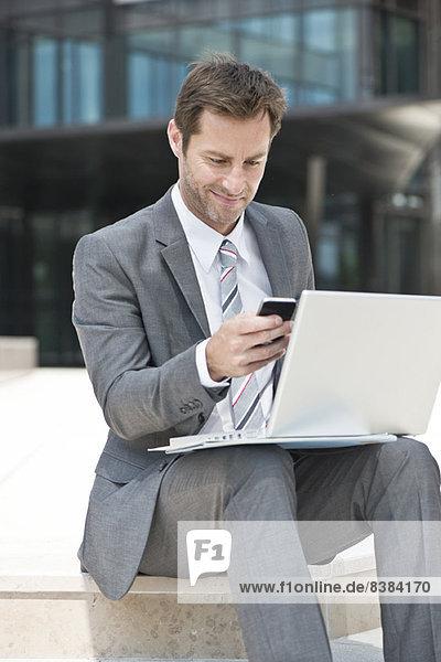 Geschäftsmann Multitasking bei der Arbeit im Freien