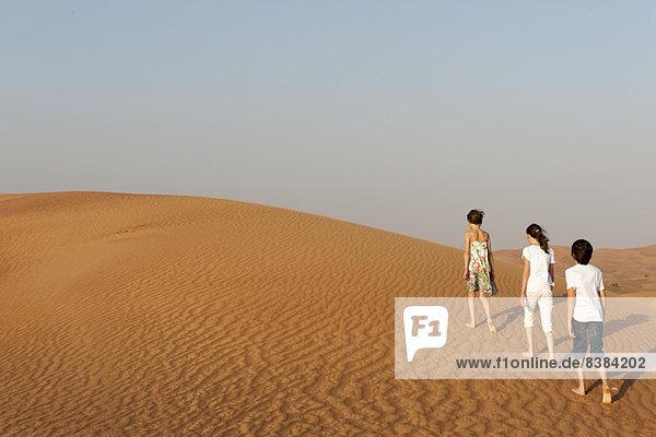 Kinder wandern in der Wüste  Rückansicht
