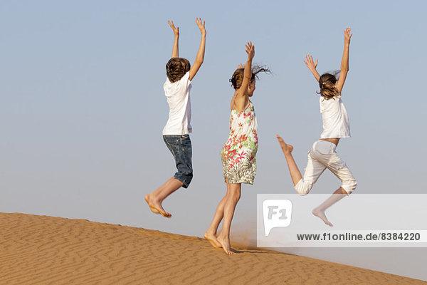 Kinder springen auf Sand  Rückansicht