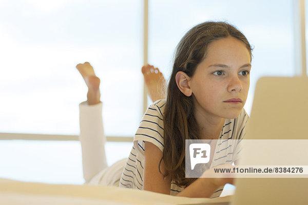 Preteen Mädchen auf dem Bauch liegend mit Laptop-Computer