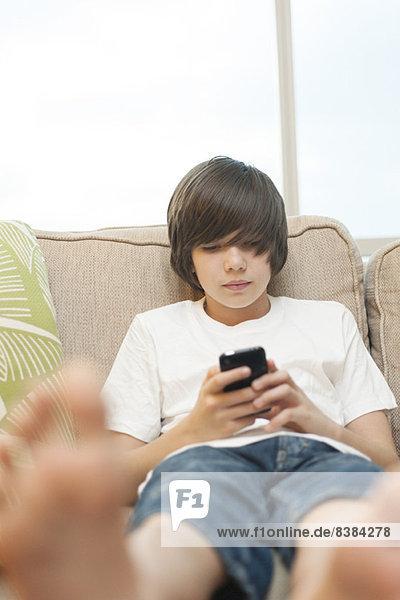 Teenager-Junge auf Sofa sitzend  mit Smartphone