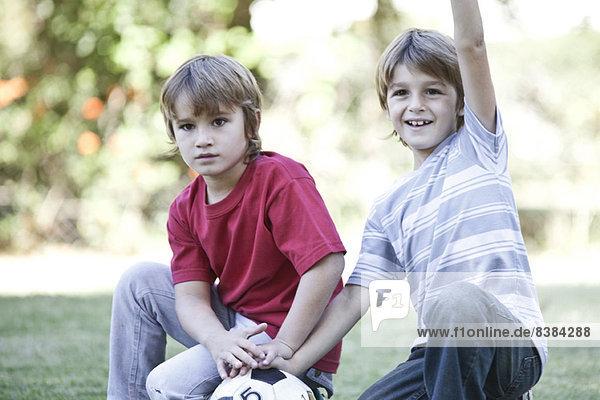 Jungen hocken auf dem Feld mit Fußball  ein Junge jubelt mit dem Arm in der Luft.