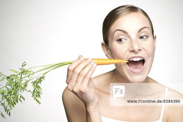 Junge Frau isst Karotte