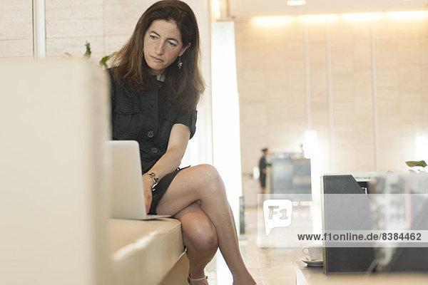 Frau mit Laptop in der Hotellobby