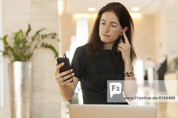Frau mit Smartphone und Kopfhörer in der Lobby