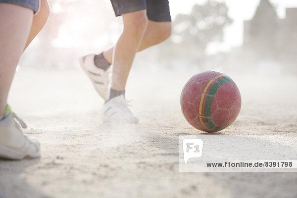 Kinder spielen mit Fußball im Sand