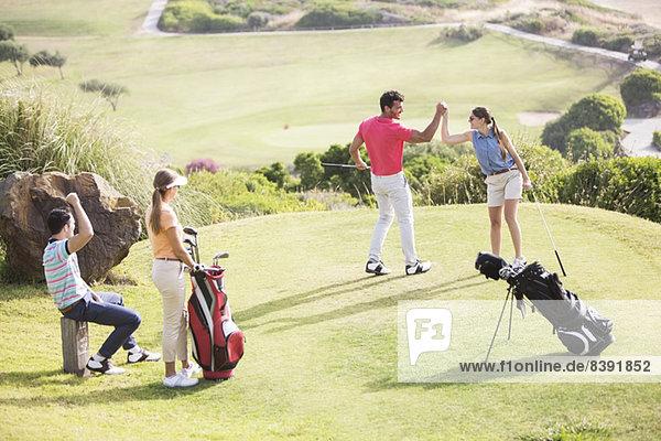 Freunde spielen Golf auf dem Platz
