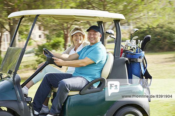 Seniorenpaar fährt Golfwagen auf dem Platz