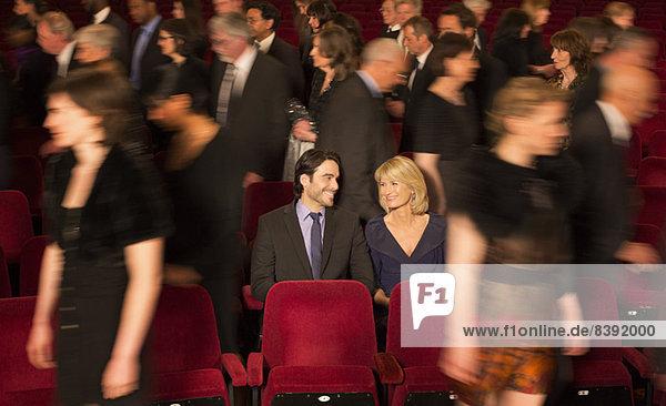 Ein Paar sitzt zwischen Menschen  die das Theater verlassen.