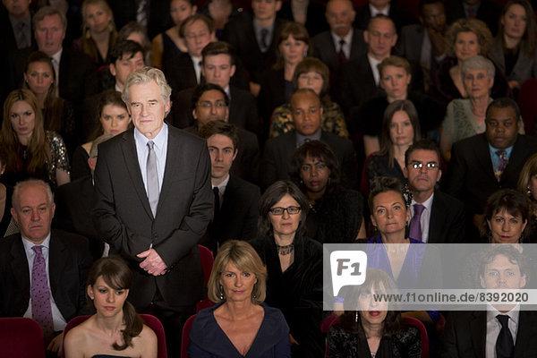 Ernsthafter Mann  der im Theater steht.